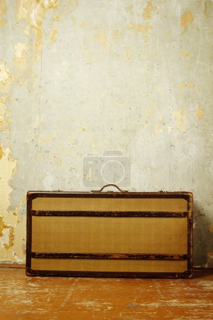 Photo for Old-fashioned suitcase standing on the old wooden floor against a shabby wall - Royalty Free Image