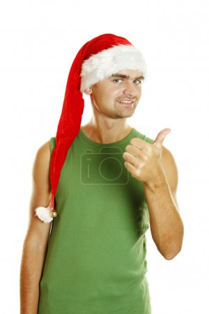 Photo for Young man in a Santa Claus hat and green poppy approvingly shows the thumb raised up. Isolated on a white background - Royalty Free Image