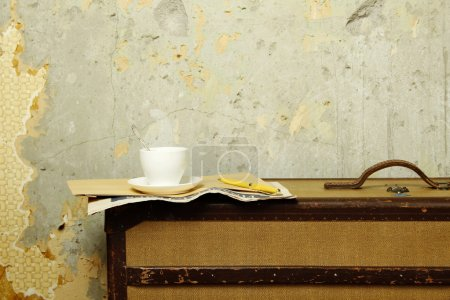 Photo for In the operation room at the edge of an old suitcase lies newspaper in which there is a cup of coffee (tea) - Royalty Free Image