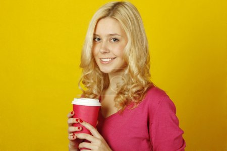 Photo for Beautiful young woman on a yellow background holding a paper cup of coffee - Royalty Free Image