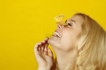 Photo for Portrait of a beautiful young woman with a butterfly on a yellow background. Isolated on a white background - Royalty Free Image