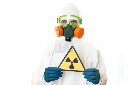 Photo for Man in protective suit, a mask and a respirator. Holding a sign warning of radiation. Isolated on white - Royalty Free Image