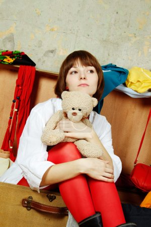 Photo for Young beautiful woman on the background of a concrete wall system sits in a big old-fashioned suitcase filled with clothes. Hugs a toy teddy - Royalty Free Image