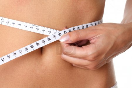 Closeup measurement of a female waist on a white background