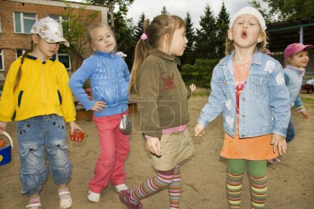 Cheerful children on walk in a kindergarten pose in the summer, looking of camera