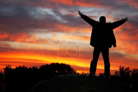 Photo for Adoration of heaven. Silhouette of the man with hands upwards, on a sunset - Royalty Free Image