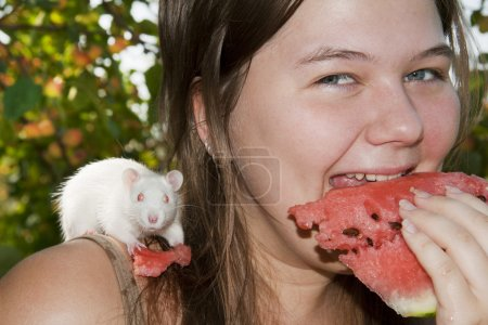 Girl and its white rat eats a water-melon