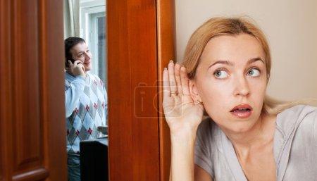 Photo pour Femme jalouse, entendant une conversation téléphonique son mari - image libre de droit