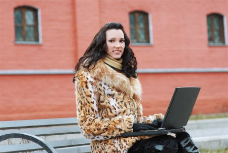 Brunette with laptop outdoors
