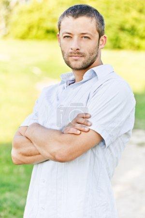 Photo pour Portrait de jeune bel homme non rasé en chemise légère contre le parc vert d'été . - image libre de droit