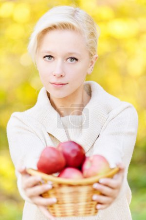 Girl offer basket with apples