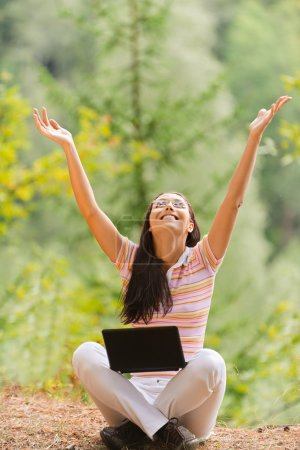 Photo for Young beautiful woman sits in pose of lotus with laptop and joyfully lifts hands upwards in summer green park. - Royalty Free Image