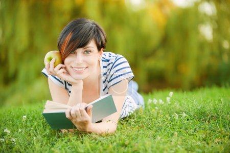 Photo pour Une belle jeune fille avec une pomme couchée sur l'herbe et lisant un livre sur fond de nature verte - image libre de droit