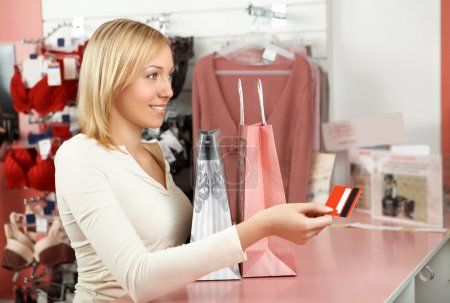 Photo for The blonde with packages in an underwear boutique holds a credit card in a hand - Royalty Free Image