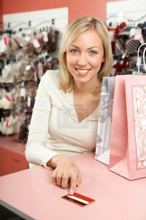 Photo for The woman in shop with packages smiles and holds in a hand a credit card - Royalty Free Image