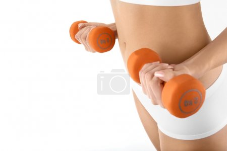 Photo for The hand close up is held by dumbbells against a stomach, isolated - Royalty Free Image