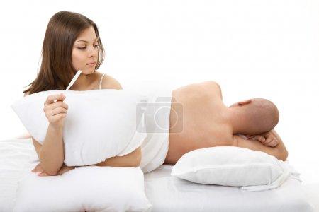 Photo pour La femme regarde l'homme endormi ne connaissant pas sa grossesse - image libre de droit
