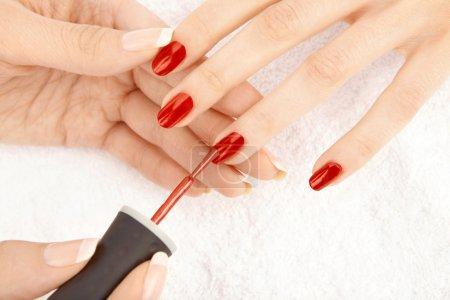 Photo pour La main féminine pose un vernis sur les ongles des doigts féminins, isolés - image libre de droit