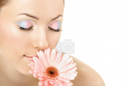 Photo for The girl brings a flower to a nose, isolated - Royalty Free Image