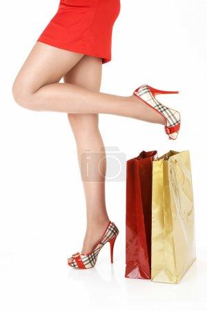 Photo pour Vue latérale des jambes féminines près des paquets - image libre de droit