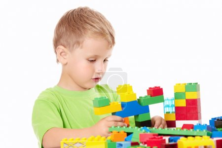 Little boy builds something of the plastic multi-coloured parts, isolated