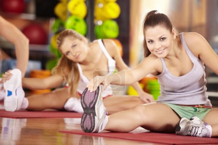 Two smiling girls do exercise in sports club...