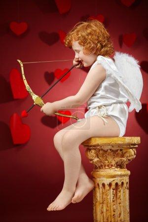 Photo pour Voir le profil:: le petit garçon visée - le Cupidon sur fond rouge - image libre de droit