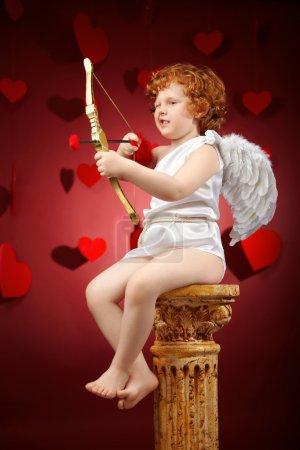 Photo pour Petit garçon visant à une image de l'amour sur un fond rouge - image libre de droit