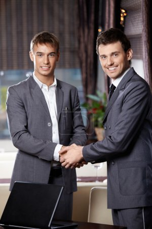 Photo for Two smiling business men shake hands each other at a meeting at restaurant - Royalty Free Image