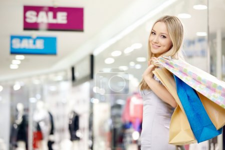 Photo for Attractive smiling blonde on shopping in shop - Royalty Free Image