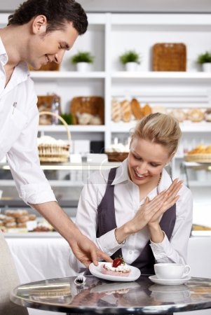 Photo for The waiter brings to the visitor the ordered dessert - Royalty Free Image