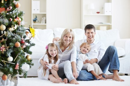 Photo for Young laughing family home with spruce - Royalty Free Image