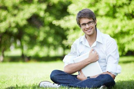 Foto de Un joven empresario con una laptop en la hierba - Imagen libre de derechos