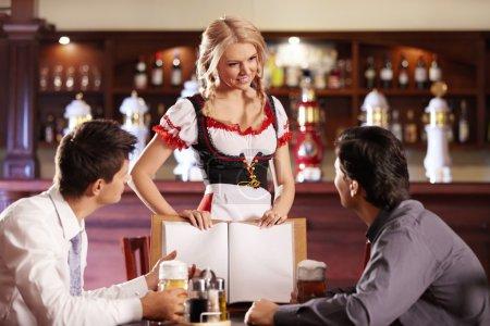 Photo for Attractive waitress shows visitors the menu bar - Royalty Free Image