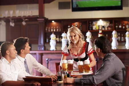 Photo for The waitress brings the men to beer in the beer garden - Royalty Free Image