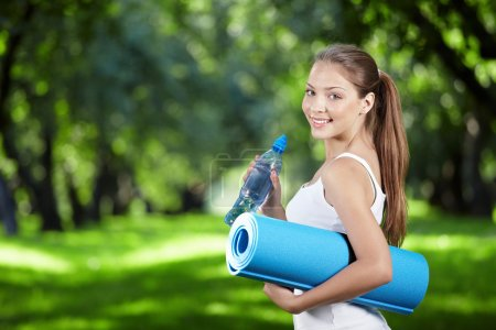 Photo for Young girl with a bottle of water and gym mat in the park - Royalty Free Image