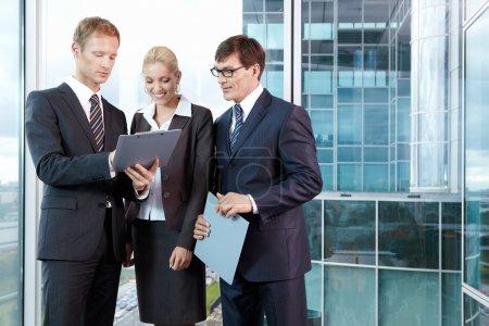 Foto de Adapte a tres hombres jóvenes en los negocios en la oficina - Imagen libre de derechos