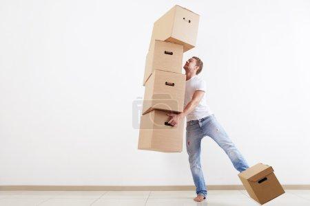 Photo pour Un jeune homme essayant de transporter toutes les cases - image libre de droit