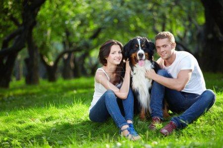 Photo pour Un beau couple avec un chien dans le parc - image libre de droit