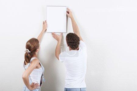 Photo pour Jeune couple raccrochant de peinture sur le mur - image libre de droit