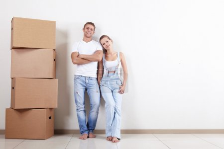 Photo for Young happy couple with boxes in apartment - Royalty Free Image