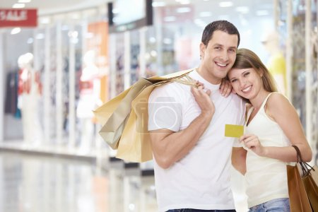 Photo for The happy couple with a credit card and shopping at the store - Royalty Free Image