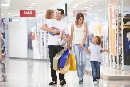 Photo for A young family of four with children in the store - Royalty Free Image
