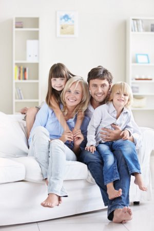 Photo for A happy family with children on a white sofa at home - Royalty Free Image