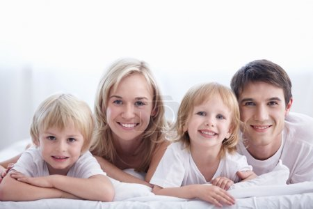 Photo for A happy family on white bed in the bedroom - Royalty Free Image