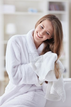 Photo pour Une belle jeune fille en peignoir essuie ses cheveux avec une serviette - image libre de droit