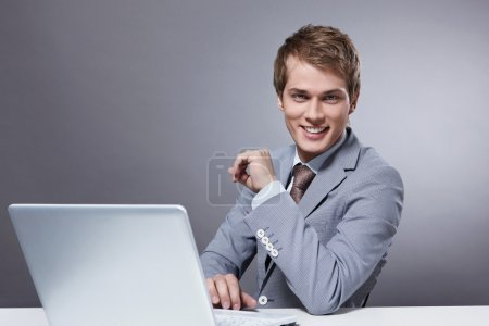 Photo for Attractive young man with a laptop on a gray background - Royalty Free Image