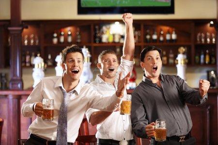 Photo pour Jeunes avec de la bière à regarder le football dans un bar - image libre de droit