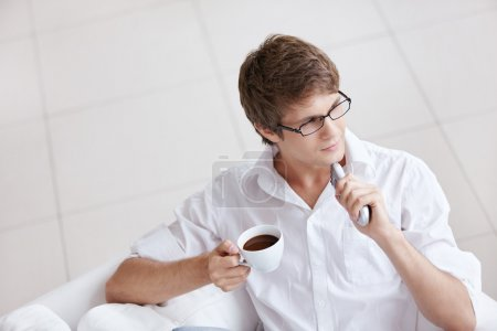 Photo for A young man with a cup of coffee and a remote control in hand - Royalty Free Image