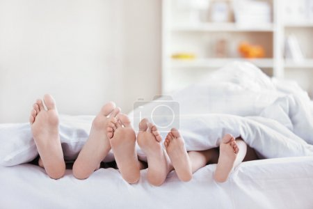 Photo for Legs sticking out from under the blankets in the bedroom - Royalty Free Image